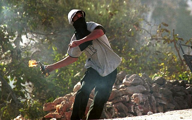 Ilustrative: A Palestinian youth hurls a Molotov cocktail at IDF soldiers near Bethlehem in 2000. (Yossi Zamir/Flash90)