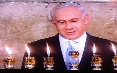 Prime Minister Benjamin Netanyahu lights Hanukkah candles in the Old City on Saturday, the last night of the festival (photo credit: Channel 2 screenshot)
