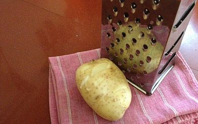 Grate some potato into a clean dishtowel for relieving inflammation (photo credit: Jessica Steinberg/Times of Israel)