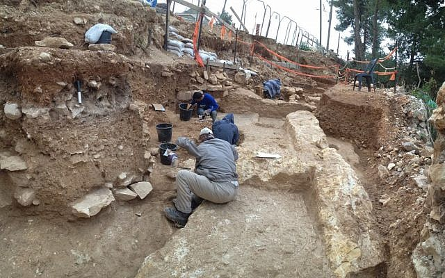 Workers uncover the foundations of ancient buildings under a road in the Jerusalem neighborhood of Kiryat Hayovel (Courtesy of the Israel Antiquities Authority)