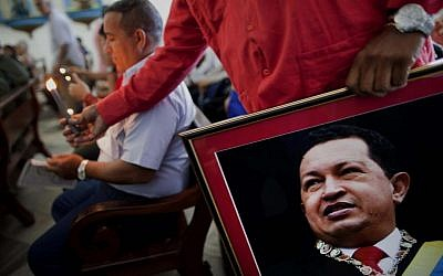 A Venezuelan Embassy worker holds a framed image of Venezuela's ailing President Hugo Chavez in Havana, Cuba, earlier this month (photo credit: AP/Ramon Espinosa)