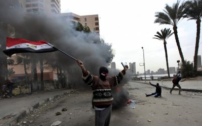 A protester, part of the Black Bloc, holds the Egyptian national flag during clashes with riot police near Tahrir Square, Cairo, Egypt, Monday, Jan. 28, 2013 (photo credit: AP/Khalil Hamra)
