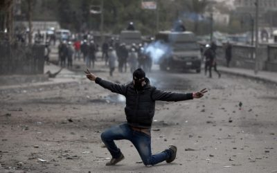 A masked Egyptian protester part of the Black Bloc, flashes the victory sign during clashes with riot police, background, near Tahrir Square, Cairo, Egypt, Monday, Jan. 28, 2013 (photo credit: AP/Khalil Hamra)