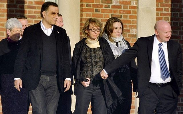 Former US Rep. Gabrielle Giffords, center, holds hands with her husband, Mark Kelly, while exiting Town Hall in Newtown, Conn. after meeting with city officials Friday. Giffords also met with families of the victims of the Sandy Hook Elementary massacre that left 26 people dead. (photo credit: AP Photo/The News-Times, Jason Rearick)