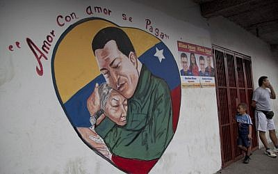 "A heart-shaped mural shows an image of Venezuela's President Hugo Chavez hugging a woman. Chavez hasn't spoken publicly or been seen since his Dec. 11 operation in Cuba, and the latest report from his government Thursday night increased speculation that he is unlikely to attend his Jan. 10 inaugural ceremony. The message above the mural reads in Spanish; ""Love is repaid with love."" (AP Photo/Ariana Cubillos)"