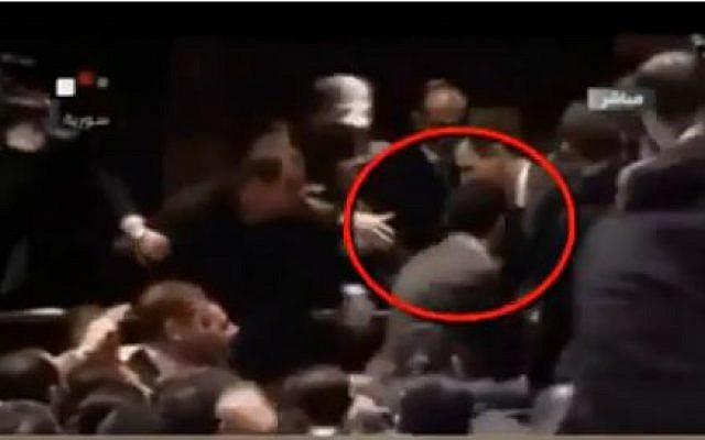 Syrian President Bashar Assad receiving an inadvertant head butt from his body guard (YouTube screen capture)