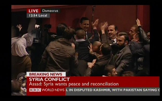 Syrian President Bashar Assad waves at supporters in Damascus's Opera Hall on Sunday, Jan. 6 (image capture: BBC)