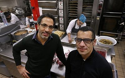 Chefs Yotam Ottolenghi, left, and Sami Tamimi, right, pose for the photographer at their company's bakery in London. (photo credit: AP/Lefteris Pitarakis)