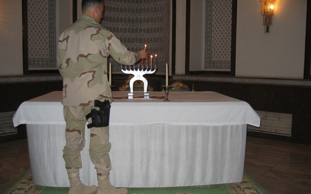 Maj. Elan Carr lights Hanukkah candles in late 2003 in a Baghdad palace formerly inhabited by Saddam Hussein. (Courtesy of Elan Carr)