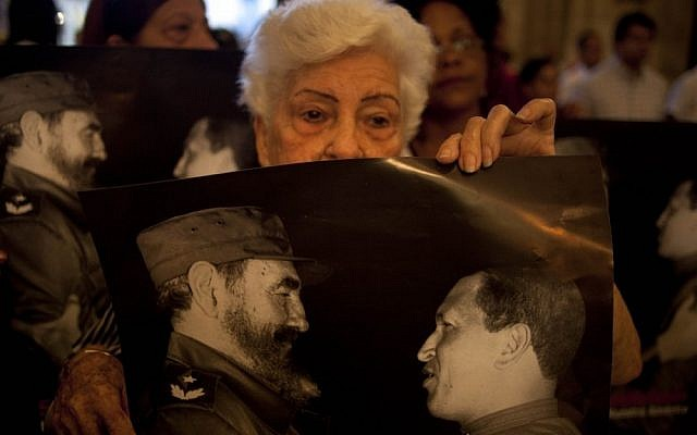 Parishioners hold posters that show Cuba's Fidel Castro, left, and Venezuela's President Hugo Chavez, during a mass to pray for the recovery of Chavez at the Cathedral, in Havana, Cuba, in January 2013 (photo credit: AP/Ramon Espinosa)