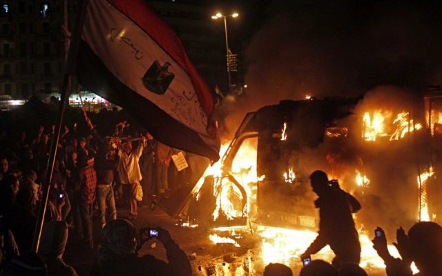 Egyptian protesters and a burning state security armored vehicle that demonstrators commandeered, brought to Tahrir Square and set alight, January 28 (photo credit: Mostafa El Shemy/AP)