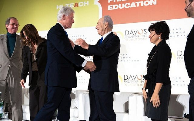 President Shimon Peres shakes hands with former US President Bill Clinton, during a meeting at the World Economic Forum in Davos, Switzerland, in 2010 (Photo credit: Sergei Illin/Flash 90)