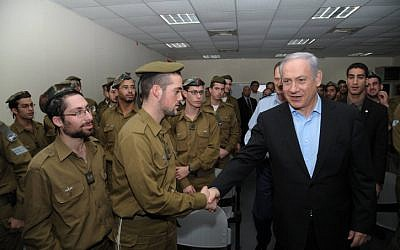 Prime Minister Benjamin Netanyahu speaks with soldiers serving in the IDF's religious unit. (photo credit: Amos BenGershom/GPO/Flash90)