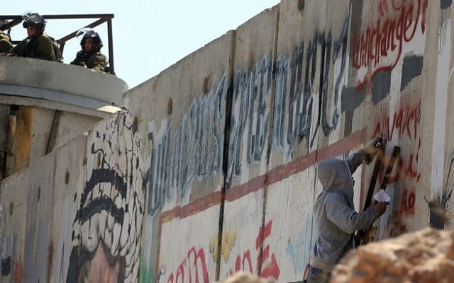An illustrative photo of an activist painting graffiti on the security barrier during a protest near the Qalandiya checkpoint between Ramallah and Jerusalem. (photo credit: Issam Rimawi/Flash90)