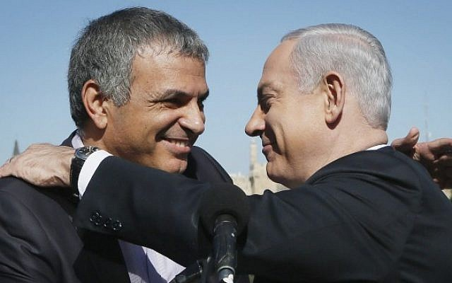Prime Minister Benjamin Netanyahu embraces outgoing Communications and Welfare Minister Moshe Kahlon, during a press conference on January 21, 2013. (photo credit: Miriam Alster/Flash90)