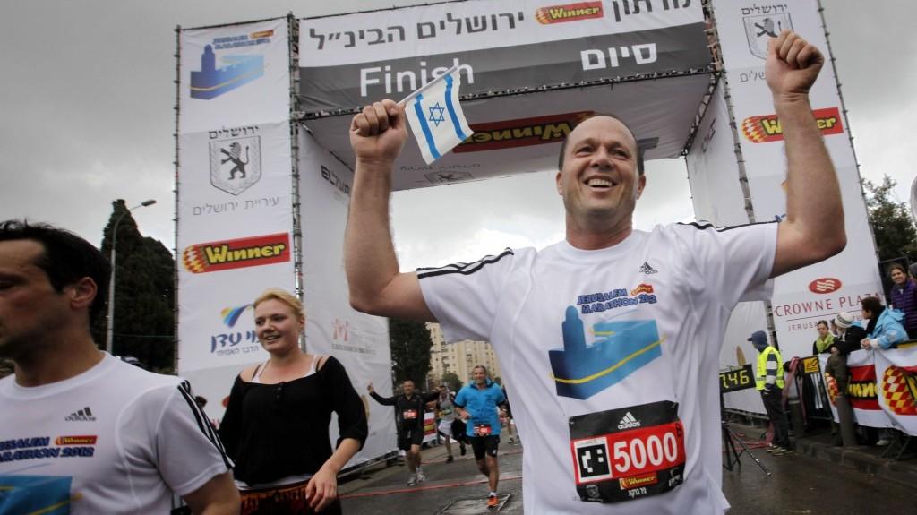 Mayor of a 'normal' city: Nir Barkat finishes the half-marathon, during the International Jerusalem Marathon last March. (photo credit: Miriam Alster/Flash90)