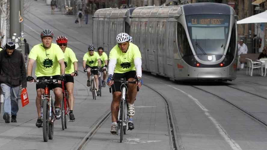 Nir Barkat rides his bicycle down Jaffa Road, with the light rail in the background. (photo credit: Uri Lenz/Flash90)