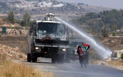 Palestinian demonstrators run from a foul smelling water fired by Israeli security forces during clashes at a protest in the West Bank, July, 2012. (photo credit:Issam Rimawi)