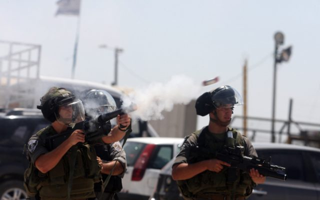 Israeli security personnel fire tear gas at Palestinian protesters, August, 2012. (photo credit: Issam Rimawi/Flash90)