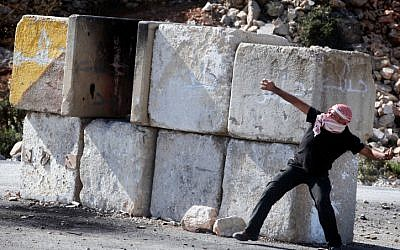 Palestinian protesters throw stones at Israeli security forces, November, 2012. (photo credit: Issam Rimawi/FLASH90)