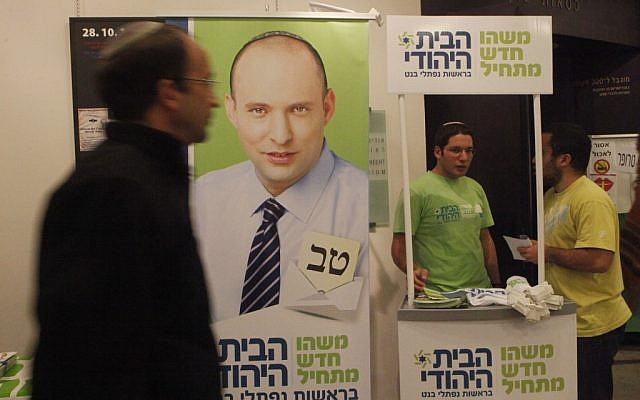 A man walking by a booth for Jewish Home in Jerusalem in December. (photo credit: Miriam Alster/Flash90)
