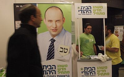 A man walks by a poster depicting Jewish Home leader Naftali Bennett, at an election conference in Jerusalem on December 23, 2012. (photo credit: Miriam Alster/Flash90)