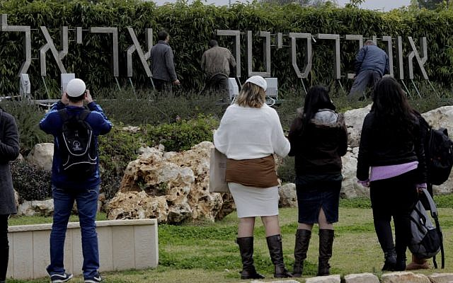 Students watching workers put up a new sign at Ariel University in December 2012. (photo credit: Amir Levy/Flash90)