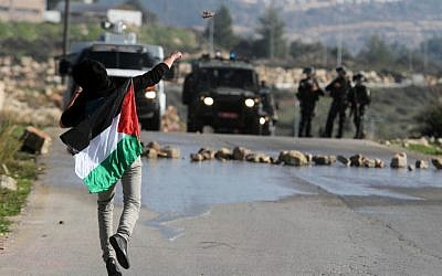 A Palestinian throwing stones at Israeli troops in the West Bank in December. (photo credit: Issam Rimawi/Flash90)