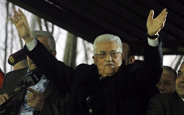 Palestinian Authority President Mahmoud Abbas waves to Fatah supporters during a rally marking the 48th anniversary of the movement's founding in Ramallah, December 31 (photo credit: Issam RImawi/Flash90)