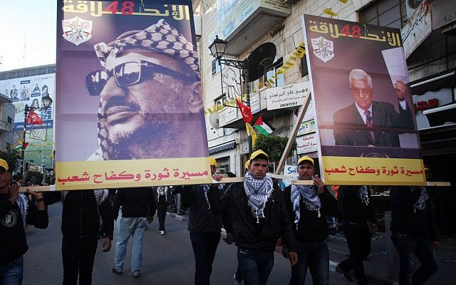 Palestinians marching with posters of Yasser Arafat, left, and Mahmoud Abbas at a Fatah rally in Ramallah in January 2013. (photo credit: Issam Rimawi/Flash90)
