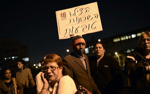 Illustrative photo of protesters holding up a sign that reads 'Help! The neighborhoods are sinking,' at an anti-migrant demonstration in Tel Aviv (photo credit: Tomer Neuberg/Flash90)