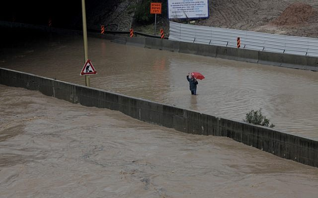 A man waves from the knee-deep water that covers the Ayalon Highway in Tel Aviv on Tuesday, Jan. 8 (photo credit: Flash90)