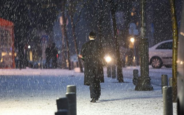 An ultra-Orthodox jewish man walks in the snow on a Jerusalem street, Wednesday, January 9, 2013 (photo credit: Yonatan Sindel/Flash90)