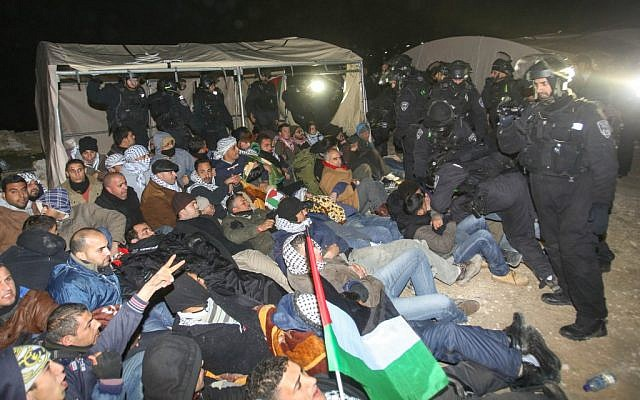 Israeli Border Police remove a Palestinian from an outpost of tents in an area known as E1, near Jerusalem, January 13, 2013. (photo credit: Flash90)