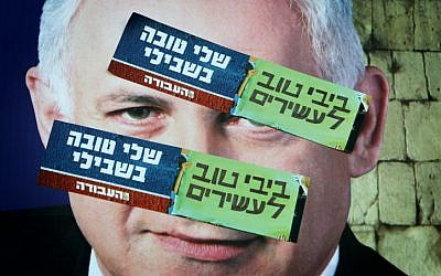 """Labor Party campaign stickers saying """"Bibi is good for the rich, Shelly is good for me"""" posted on top of a campaign poster depicting Prime Minister Benjamin Netanyahu (Miriam Alster/Flash90)"""