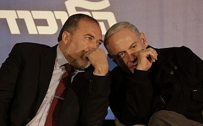 Avigdor Liberman, left, and Benjamin Netanyahu sharing a private word on Tuesday. (photo credit: Tsafrir Abayov/Flash90)