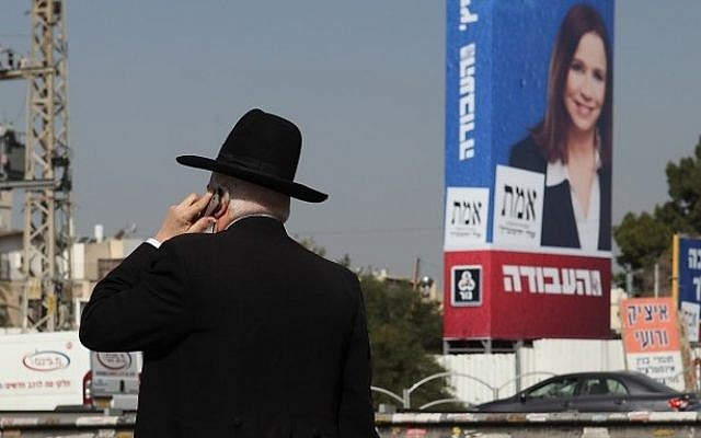 An ultra-Orthodox Jewish man seen next to a large election campaign poster showing the leader of the Labor party, Shelly Yachimovich, in the Orthodox neighborhood of Bnei Brak, Thursday. (photo credit: Yaakov Naumi/Flash90)