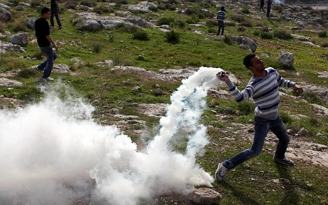 Palestinians hurl rocks at Israeli soldiers during a demonstration in the village of Budrus, west of Ramallah, Friday. (photo credit: Issam Rimawi/Flash90)