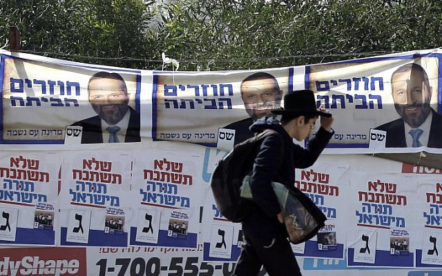An ultra-Orthodox Jewish young man passes posters of the ultra-Orthodox Shas party Friday, Jan. 18, 2013.(photo credit: Tsafrir Abayov/Flash90)