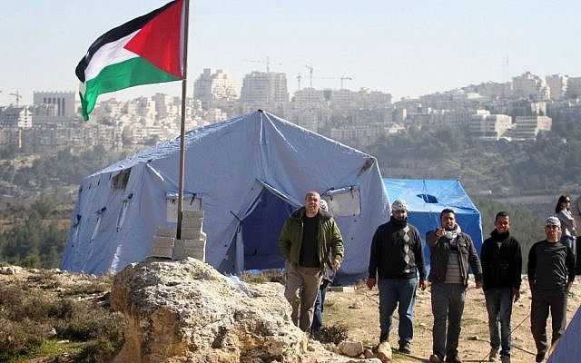 Palestinian protestors gather next to tents erected near the West Bank village of Beit Iksa, between Ramallah and Jerusalem, on Sunday (photo credit: Issam Rimawi/Flash90)