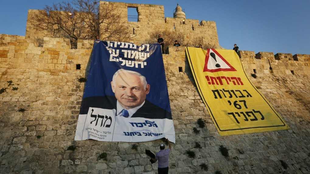"Supporters of Prime Minister Benjamin Netanyahu and his Likud party unfold large posters depicting Netanyahu reading ""Only Netanyahu will protect Jerusalem"" and ""The borders of '67 in front of you,"" at the Old City walls, January 20, 2013. (Photo credit: Miriam Alster/FLASH90)"