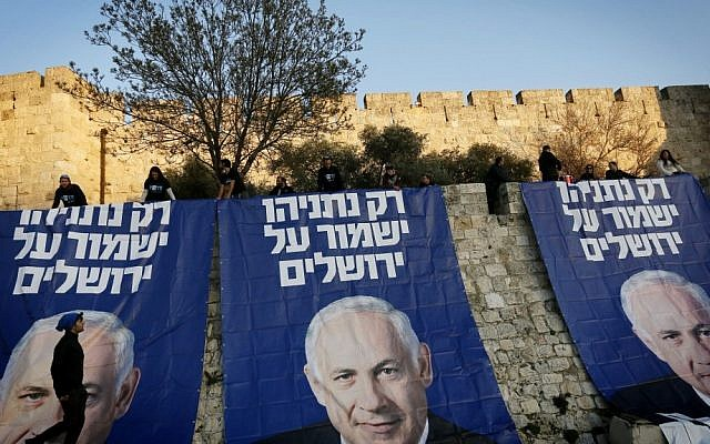"Outside the walls of Jerusalem's Old City, supporters of Prime Minister Benjamin Netanyahu unfold huge signs that read, ""Only Netanyahu will protect Jerusalem,"" on Sunday (photo credit: Miriam Alster/Flash90)"