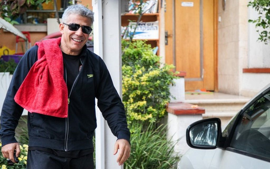 Yesh Atid leader Yair Lapid leaves his home for a pre-elections workout on Tuesday, Jan. 22 (photo credit: Avishag Shaar Yashuv/Flash90)
