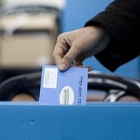 A woman places her vote in a ballot box for the Israeli general elections for the 19th parliament, January 22, 2013, in Jerusalem. (photo credit: Yonatan Sindel/Flash90, illustrative)