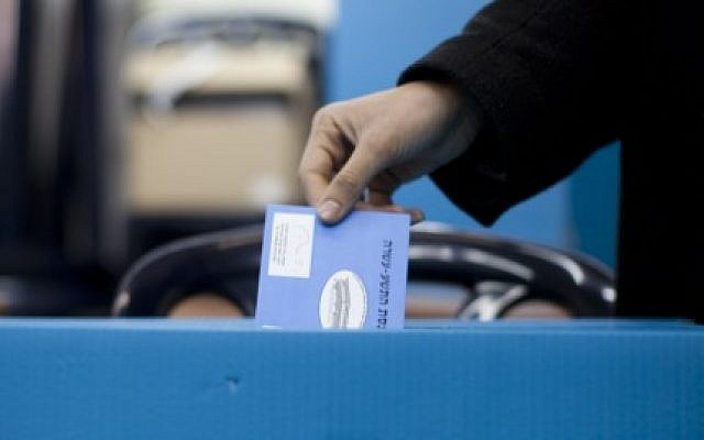 Illustrative: A woman places her vote in a ballot box for the Israeli general elections for the 19th parliament, January 22, 2013, in Jerusalem. (Yonatan Sindel/Flash90)