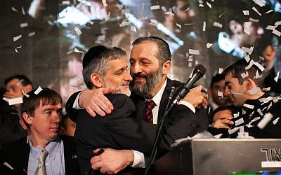 Shas chairman Eli Yishai and the party's #2, Aryeh Deri, hug at the Shas headquarters in Jerusalem as the results of the exit polls in the general elections for Israel's 19th Knesset are announced, Tuesday. (photo credit: Yonatan Sindel/Flash90)