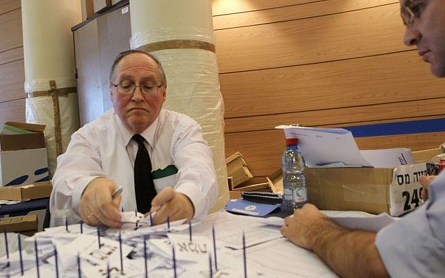 Judge Elyakim Rubinstein, head of the Central Election Committee, tallying votes in Jerusalem on Tuesday. (photo credit:  Miriam Alster/Flash90)