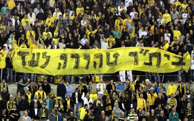Fans of the Beitar Jerusalem soccer team hold up a sign reading 'Beitar forever pure,' on Saturday, Jan 26, 2013. (photo credit: Flash90)