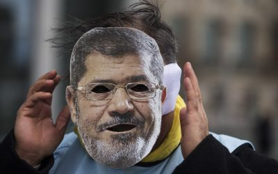 A man covers his face with a mask of Egypt President Mohammed Morsi during a protest in front of the chancellery in Berlin, Germany, Wednesday, Jan. 30, 2013. (photo credit: AP/Markus Schreiber)