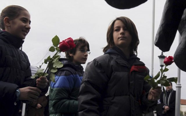 Greek children place flowers at the Holocaust Memorial commemorating the persecution of the Jewish people during World War II, in Thessaloniki, Sunday (photo credit: Nikolas Giakoumidis/AP)